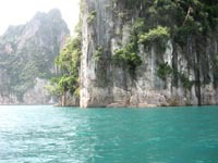 The limestone karts rise vertically from the blue-green water.
