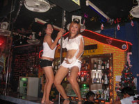 Girls dancing around a pole at a beer bar